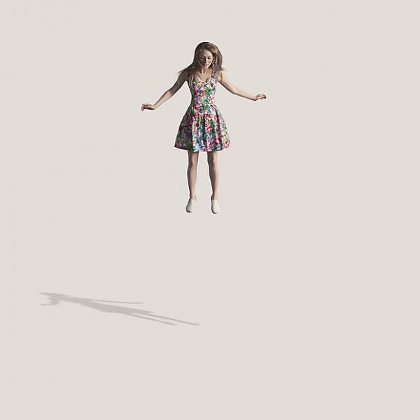 Young woman in flowery dress, jumping in the air